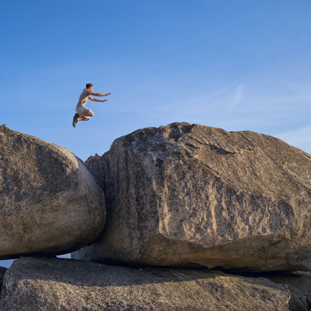 """Young Man Jumping From a Large Boulder."" stock image"