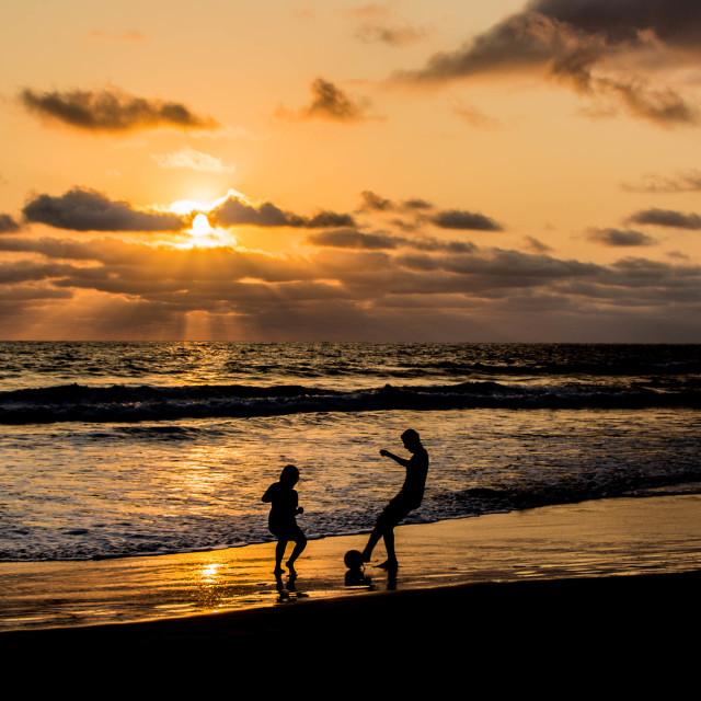 """Beach football at sunset"" stock image"