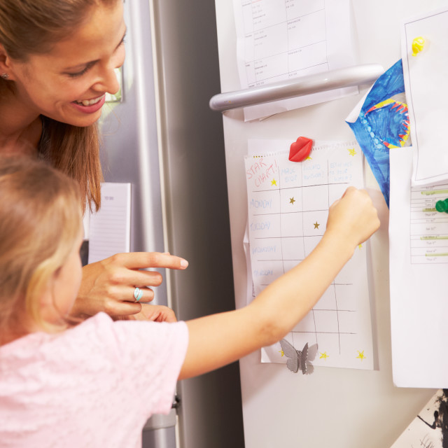 """Mother And Daughter Putting Star On Reward Chart"" stock image"