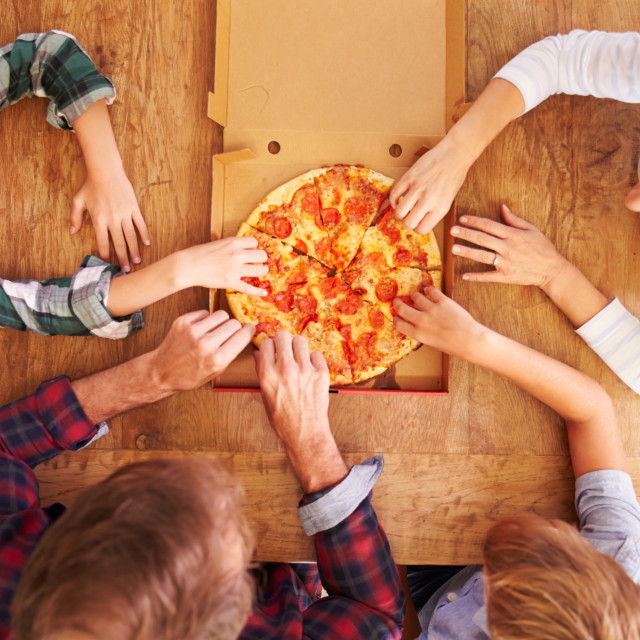 """""""Family eating pizza together, overhead view"""" stock image"""