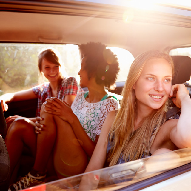 """Three Women Sitting In Rear Seat Of Car On Road Trip"" stock image"