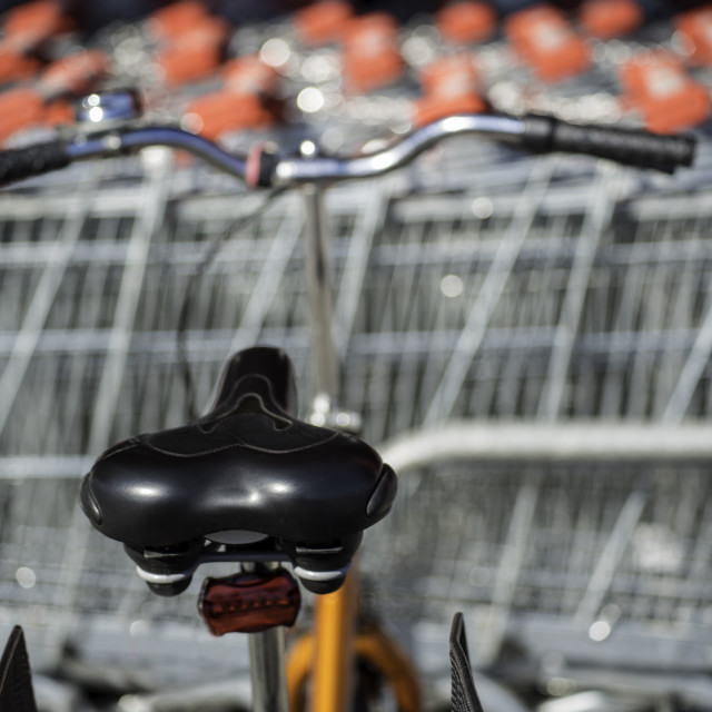 """""""Bike parked on a rack in front of store carts"""" stock image"""