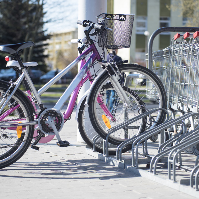 """""""Parked bikes in a parcking rack in front of supermarket"""" stock image"""