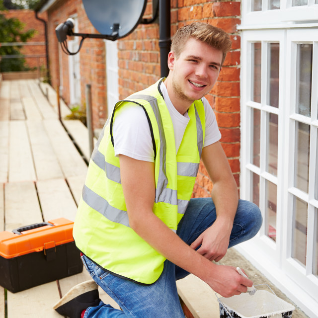"""Portrait Of Decorator On Scaffolding Painting House Windows"" stock image"