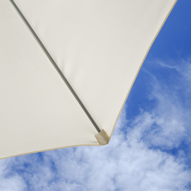 """From under a Parasol with blue sky and clouds in background."" stock image"