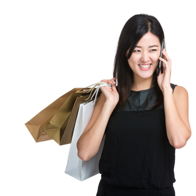 """Happy woman with shopping bag and talk to mobile phone"" stock image"