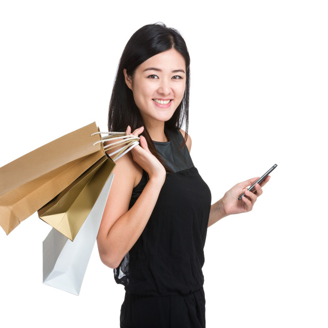 """Happy shopping woman with paper bag and mobile phone"" stock image"