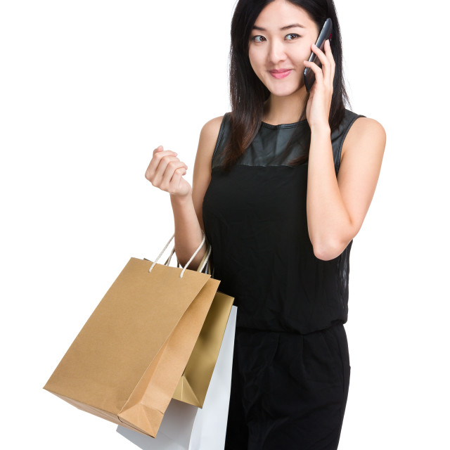 """Asian woman holding shooping bag and listen mobile phone"" stock image"