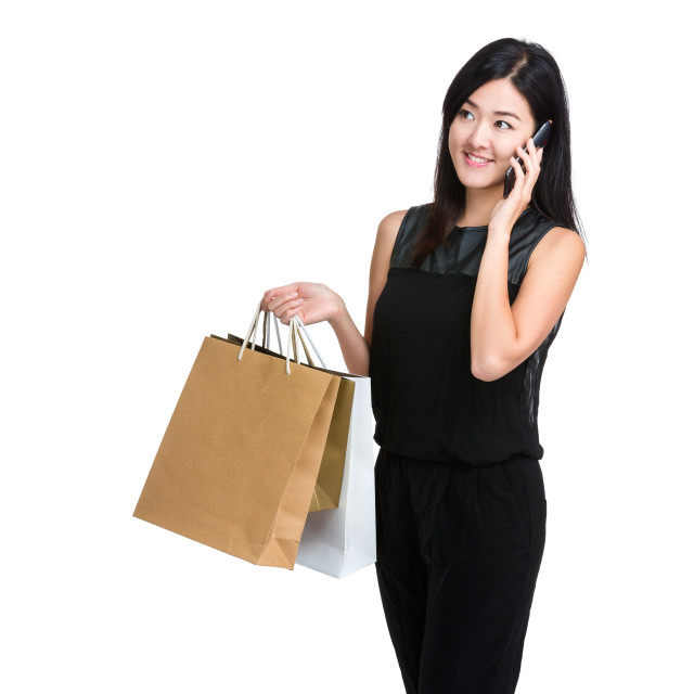"""Asian young woman talk on mobile phone with shopping bag"" stock image"
