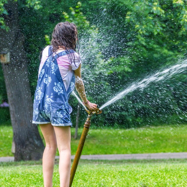 """""""Children play with automatic sprinkler watering in garden"""" stock image"""