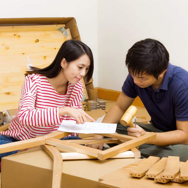 """Asian couple assembling new furniture"" stock image"