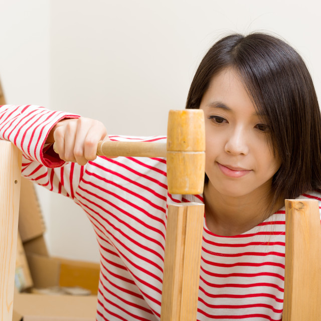 """Asian woman using hammer for new furniture assembling"" stock image"
