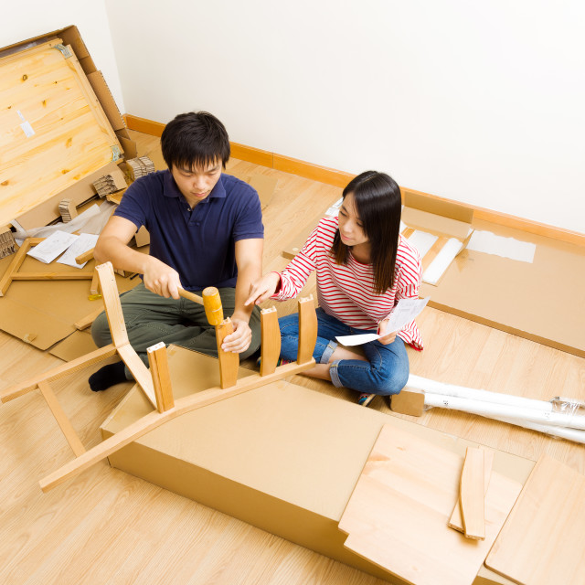 """Furniture assembling by asian couple"" stock image"