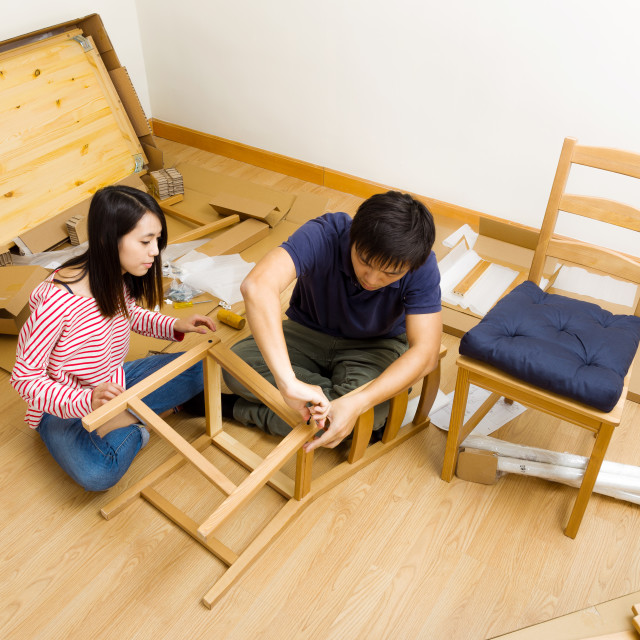 """Asian couple assembling furniture for new house"" stock image"