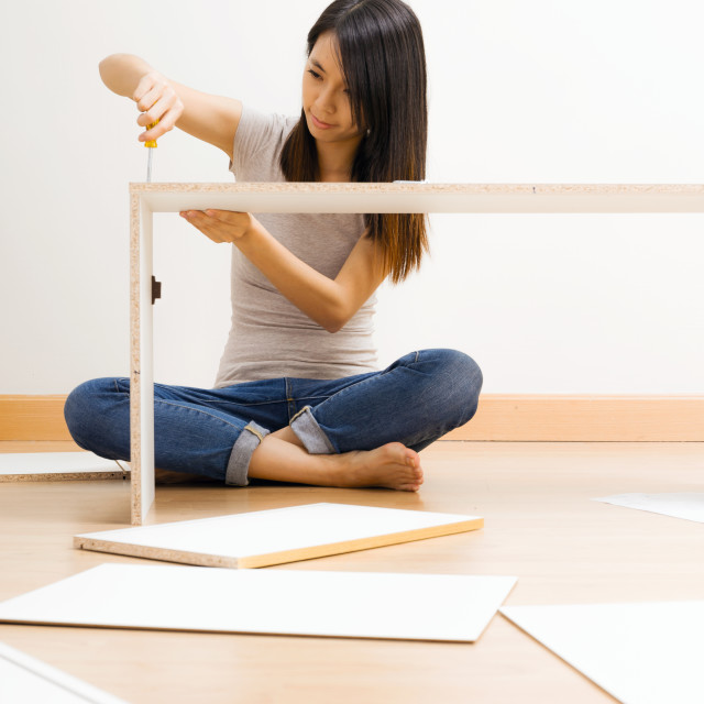 """Asian woman using strew drive for assembling closet"" stock image"