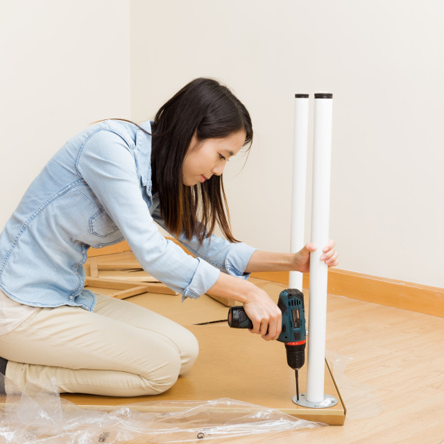 """Asian woman using strew driver for assembling furniture"" stock image"