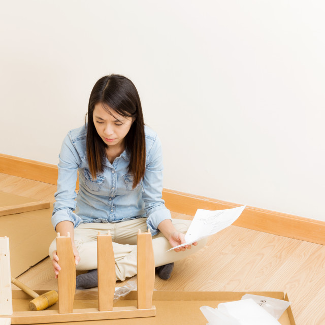 """Asian woman assembling chair by hammer with instruction"" stock image"