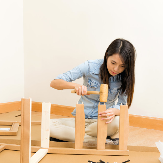 """Asian woman assembling chair by hammer"" stock image"