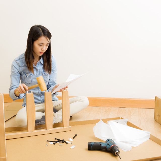 """Asian woman follow instruction for assembling chair"" stock image"