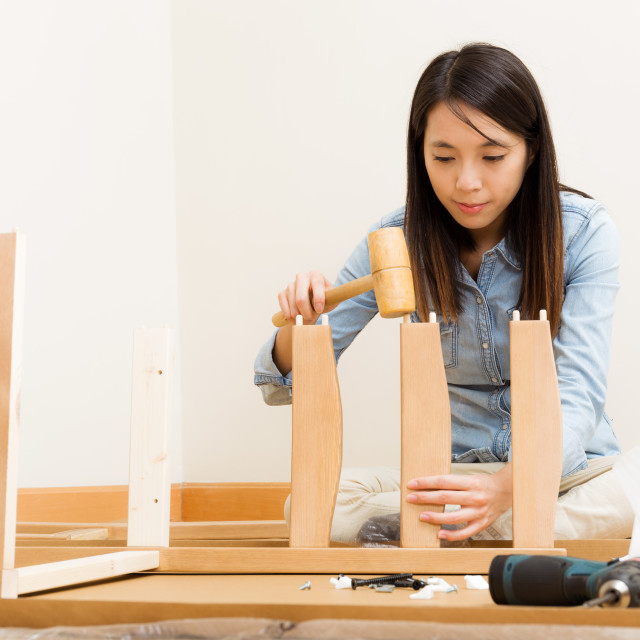 """Asian woman using hammer for assembling chair"" stock image"