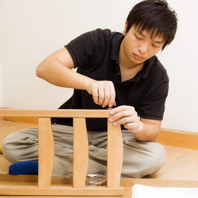 """Asian man assembling chair at home"" stock image"