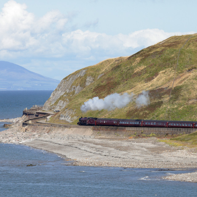 """Steam locomotive Galatea below sea cliffs at Parton Bay, Cumbria, England, UK."" stock image"