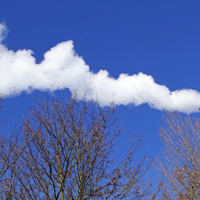 """Chimney emitting smoke against a blue sky"" stock image"