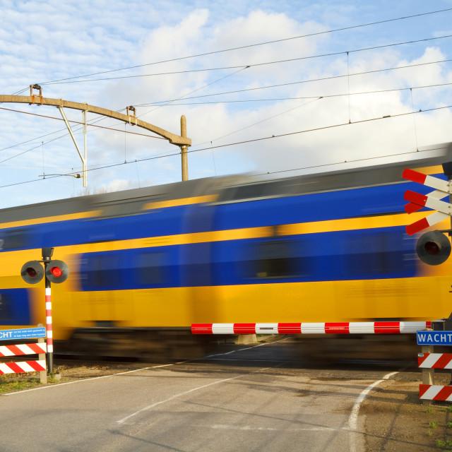 """Dutch train passing a railway crossing"" stock image"