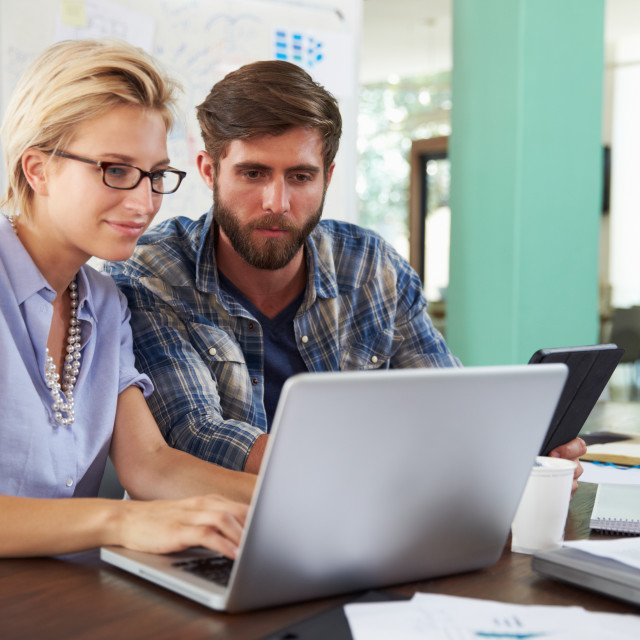 """""""Two Businesspeople Working On Laptop In Office Together"""" stock image"""
