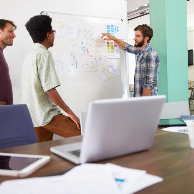 """Three Businessmen Having Creative Meeting In Office"" stock image"