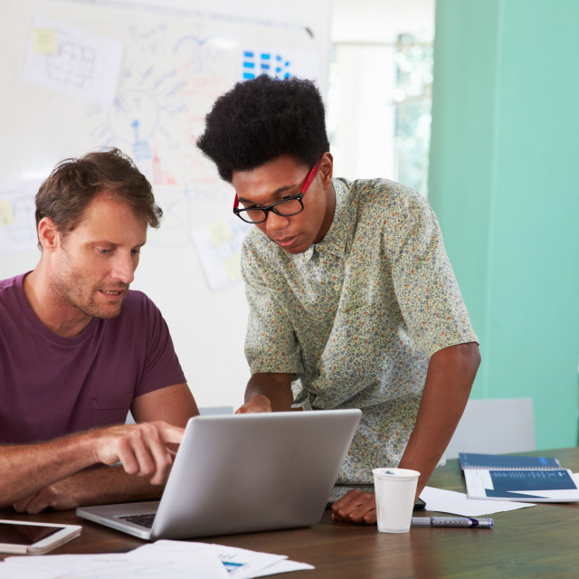 """""""Two Businessmen Working On Laptop In Office Together"""" stock image"""