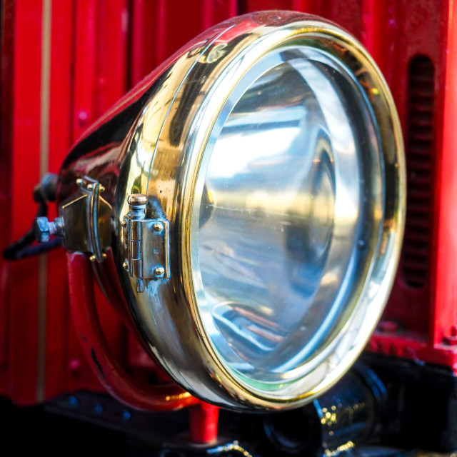 """Closeup of brass headlight with glass on old red vehicle"" stock image"