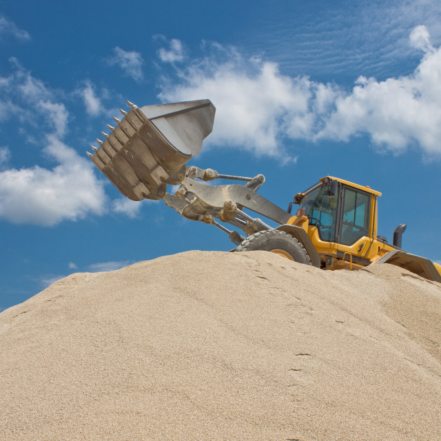 """Yellow excavator on a construction site against blue sky"" stock image"