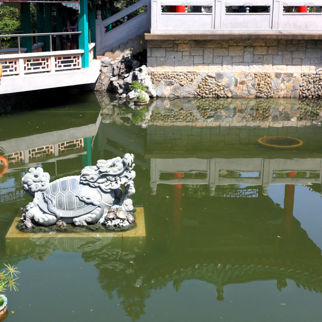 """lion statue in chinese garden pool"" stock image"