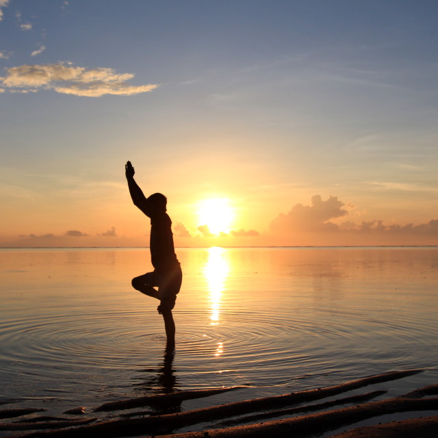 """silhouette of man doing yoga against sunrise sky"" stock image"
