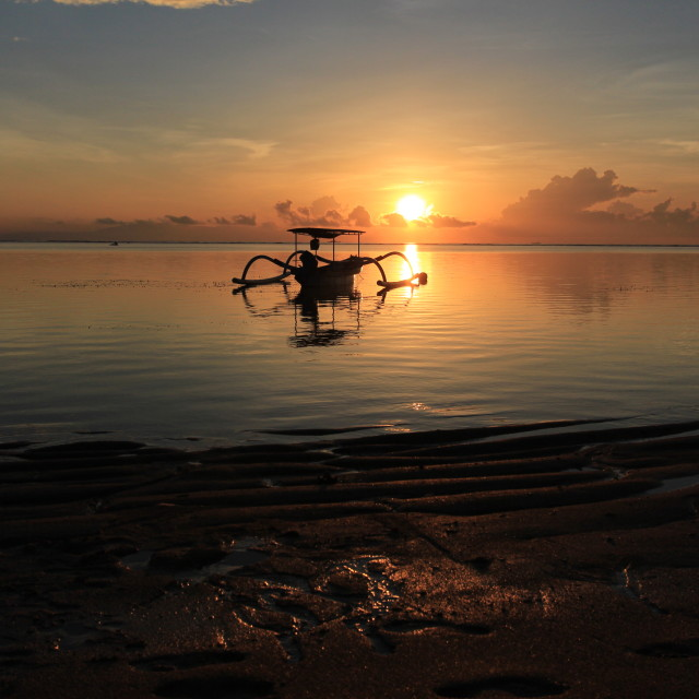 """""""view of a silhouette boat against the sunrise sky at pantai sanur bali indonesia"""" stock image"""