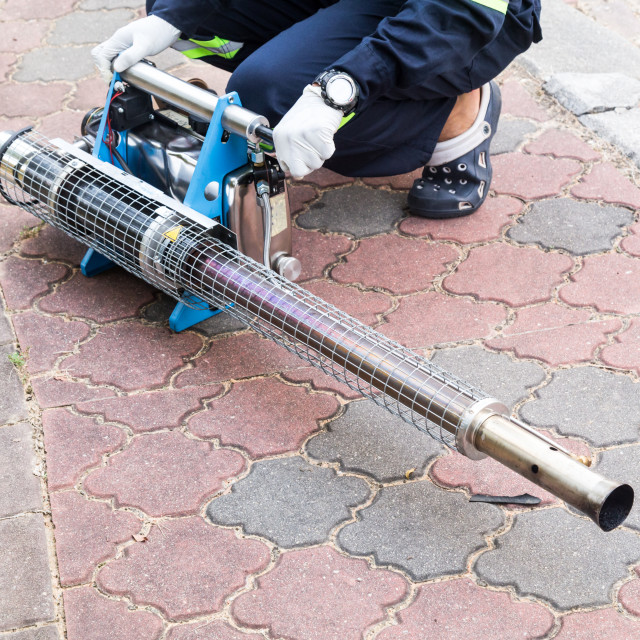 """""""Worker preparing machine to fog with insecticides to kill aedes"""" stock image"""