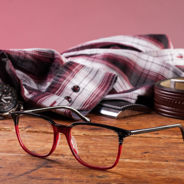 """clock, glasses and a shirt on a wooden table"" stock image"