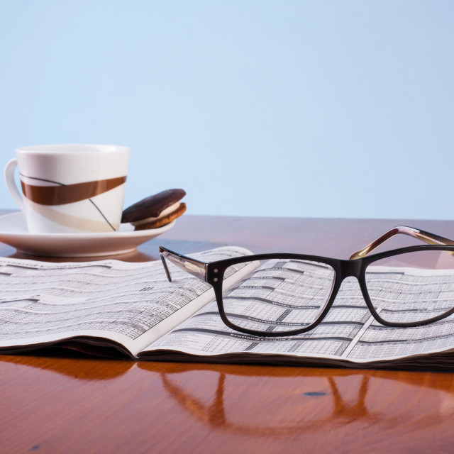 """Books, glasses and cup of coffee on a wooden table"" stock image"