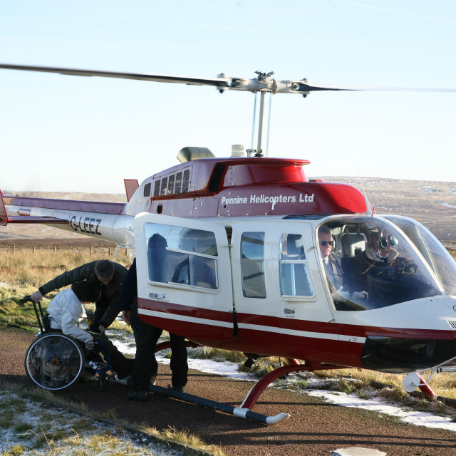 """A pleasure helicopter with a young disabled person in a wheelchair waiting to board"" stock image"