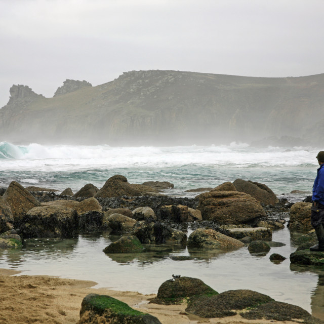 """""""A man looks out to Sea and rocks at Nanjizal or Mill Bay a Cornish cove, Cornwall, West Country, England, Winter 2010"""" stock image"""