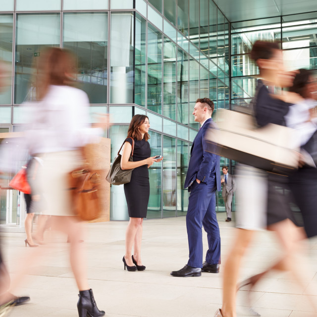 """People passing through the busy foyer of a business building"" stock image"