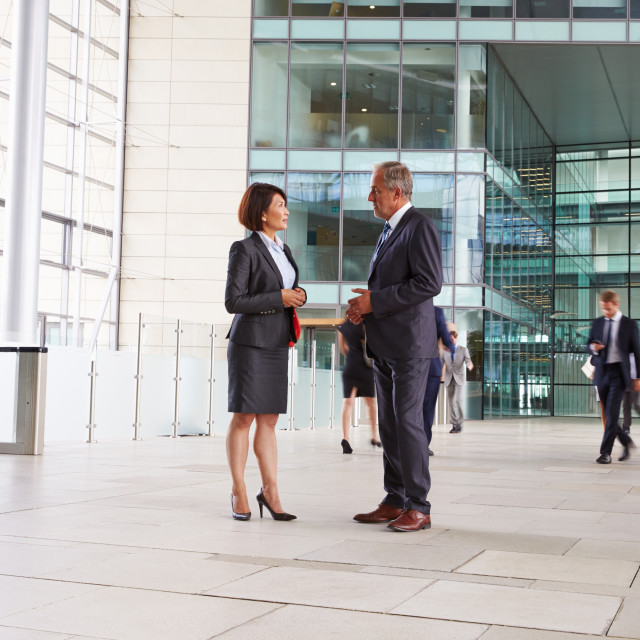 """Two senior colleagues talking in the foyer of a big business"" stock image"