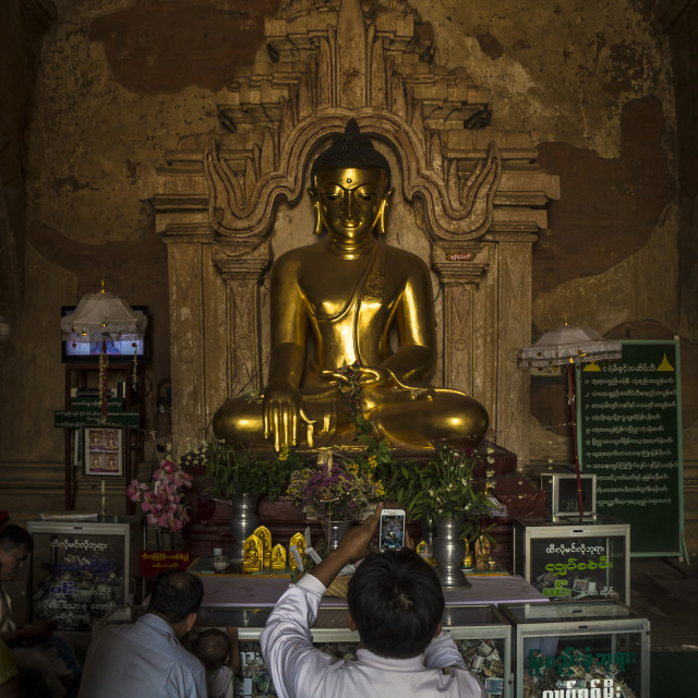 """""""Man taking photo of an ancient Buddha statue"""" stock image"""