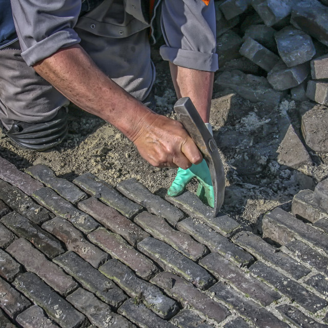 """Paving a brick road"" stock image"