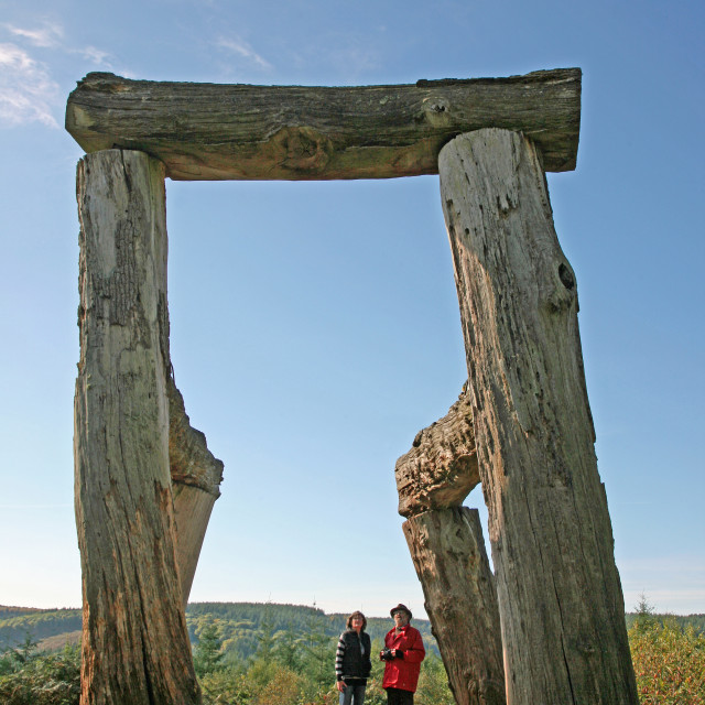 """Two people looking at an outdoor sculpture works of art in the Forest of Dean Monmouth Wales"" stock image"
