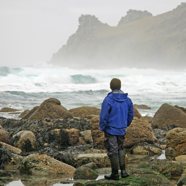 """A man looks out to Sea looking Nanjizal Mill Bay Sea and rocks at a Cornish cove Cornwall West Country England UK"" stock image"
