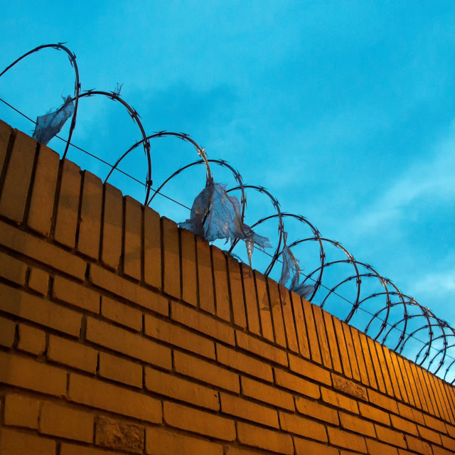 """""""Brick Fence with Barbed Wire"""" stock image"""