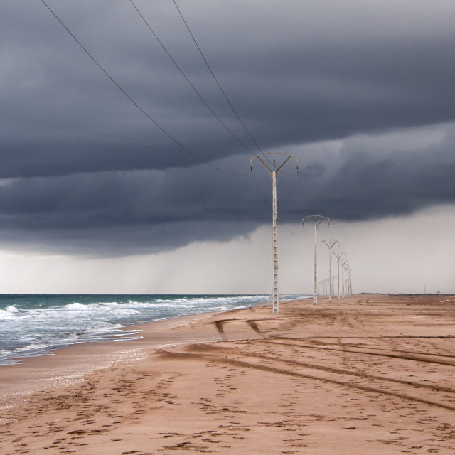 """""""Storm clouds and power lines on the beach"""" stock image"""