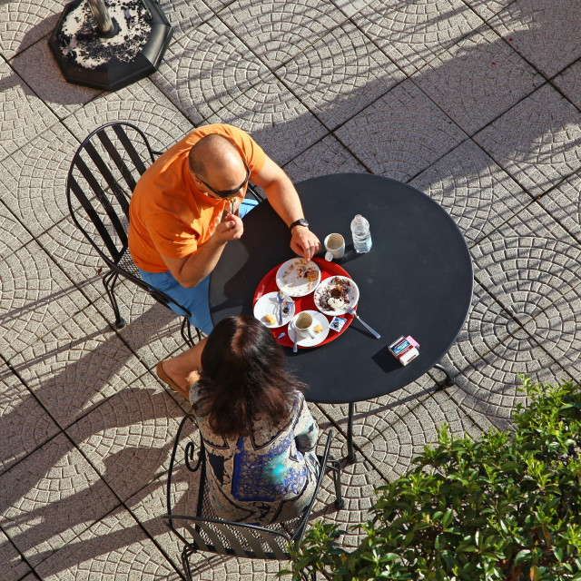 """""""Two people enjoying a cake and cup of coffee or tea sitting outdoors at a table from above in the sunshine"""" stock image"""